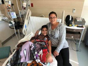 Boy and his mother sitting in a hospital bed