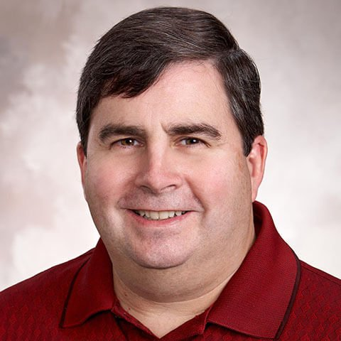 Man with short dark hair and red polo shirt on a gray photo background
