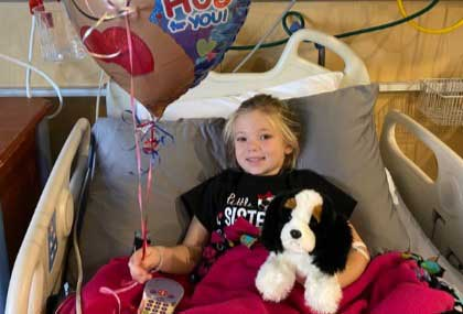 Girl in hospital bed smiling while holding a stuffed dog and balloon